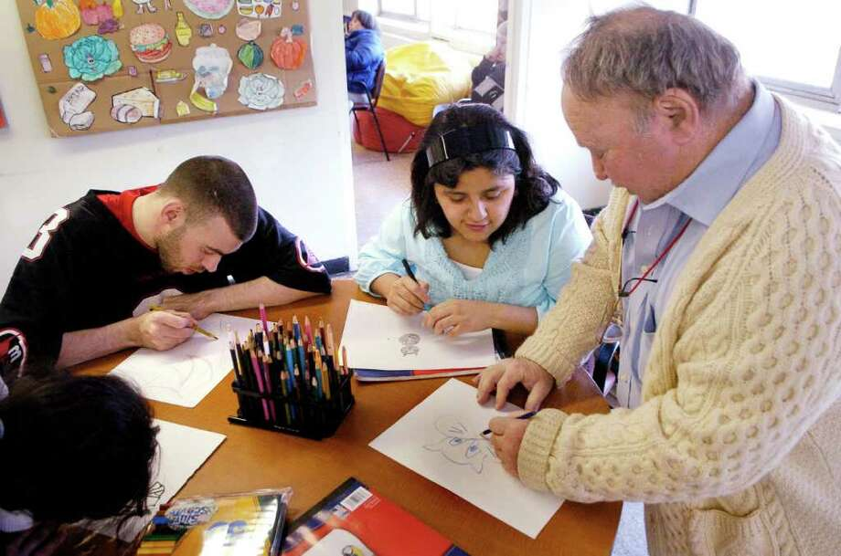 Don Axleroad, founder of the ARI Artist Initiative program, works with Mike Fox and Laura Navarrete during a session early last year. Axleroad launched the class in 2003, intially attracting four students. It has since grown to more than 20. Photo: File Photo / Stamford Advocate File Photo