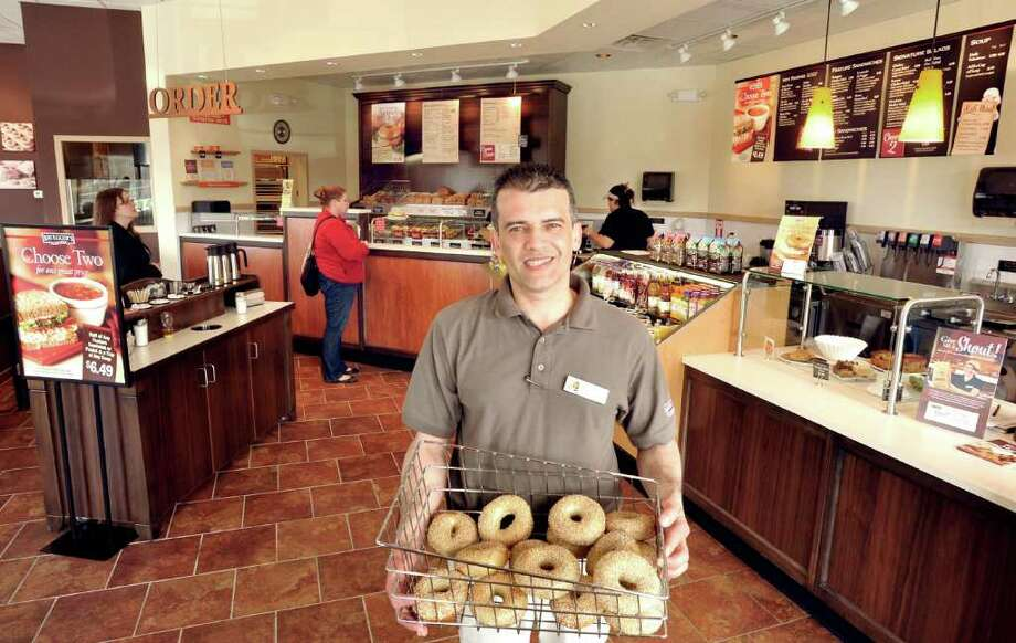 Jackson DeSouza, general manager of Bruegger's Bagels, holds a rack of bagels in the new Danbury store, Monday, April 11, 2011. Photo: Michael Duffy / The News-Times