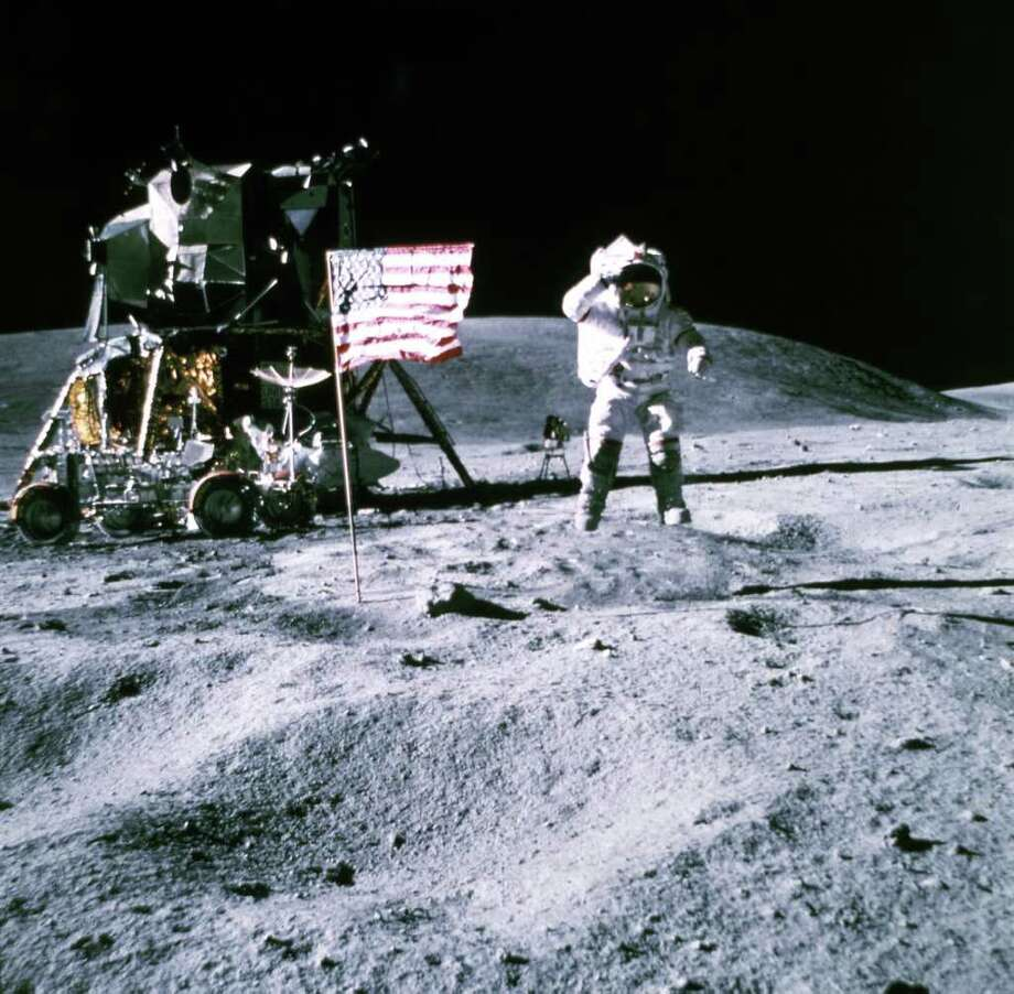 An unidentified Apollo 12 astronaut stands by the US flag on the Moon and the lunar module on November 19, 1969. Photo: -, AFP/Getty Images / 2010 AFP