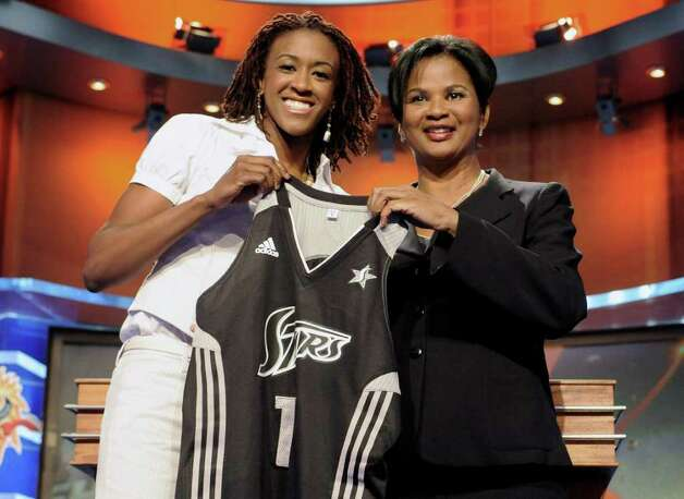 OU's Danielle Robinson (left) holds a Silver Stars jersey with WNBA official Renee Brown. Photo: Jessica Hill/Associated Press