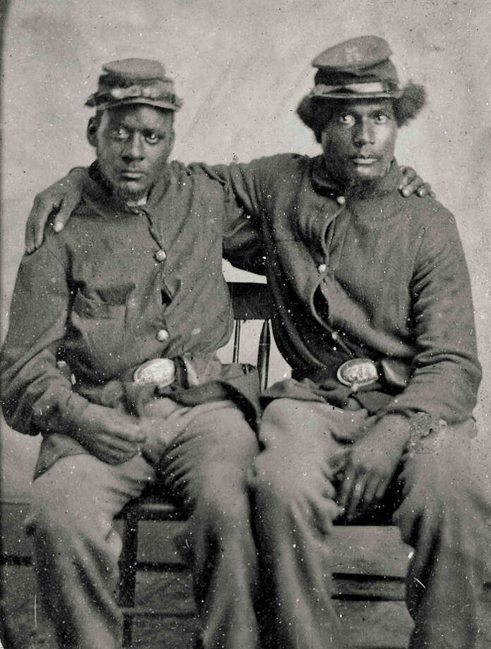 """This photograph from the Library of Congress provided by Abrams Books shows a tintype of two unidentified brothers-in-arms, African-American Union soldiers during the Civil War, in an image taken between 1860 and 1870. The image is one of nearly 500 photographs, lithographs, paintings, drawings, and cartoons from the library's collection published in a new volume, """"The American Civil War - 365 Days"""". (AP Photo/Library of Congress)"""
