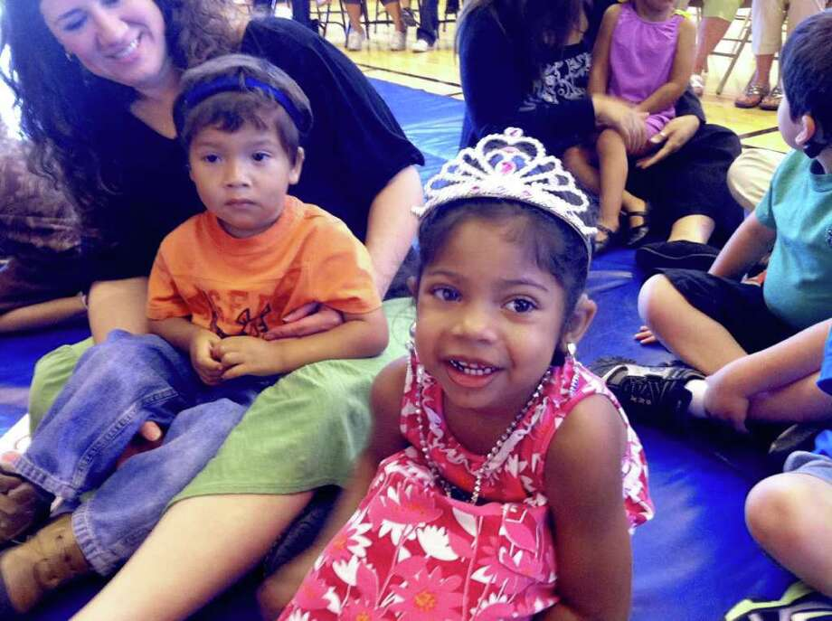 Dylan Tovar, 3, left, and Bianca Harrell, 4, right, watch the 2011 Fiesta Coronation of �The Court of Children�s Books,� on Monday at their school, Sunshine Cottage School for Deaf Children. Photo: Jennifer R. Lloyd, Jennifer R. Lloyd/Express-News