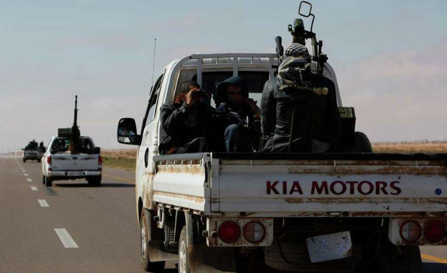 Enforcements of Libyan rebel fighters rush into the recaptured town of Ajdabiya, Libya Monday, April 11, 2011. The Libyan rebel council rejected a cease-fire proposal presented by an African Union delegation because it did not provide for the departure of Libyan leader Moammar Gadhafi and his top associates. (AP Photo/Nasser Nasser) Photo: Nasser Nasser / AP