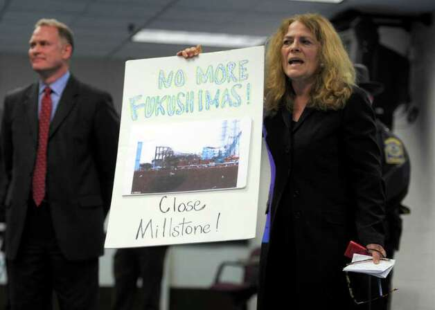 Anti-nuclear activist Nancy Burton of Mystic, right, speaks as Dan Weekley, left, vice president of governement affairs for Dominion, looks into the crowd Monday night, April 11, 2011, at Town Hall in Waterford, Conn. Millstone Power Station officials were meeting with members of the public to discuss safety issues, comparisons to the nuclear disaster in Japan and possible ramifications from proposals to raise state taxes on Millstone. (AP Photo/The Day, Tim Martin) Photo: Tim Martin, AP / The Day Publishing Company