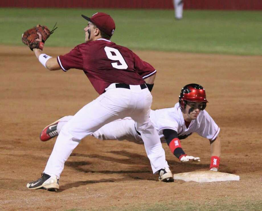 Jacob Clark waits for a pickoff throw as a Kirbyville runner dives back to first base. Photo: Jason Dunn