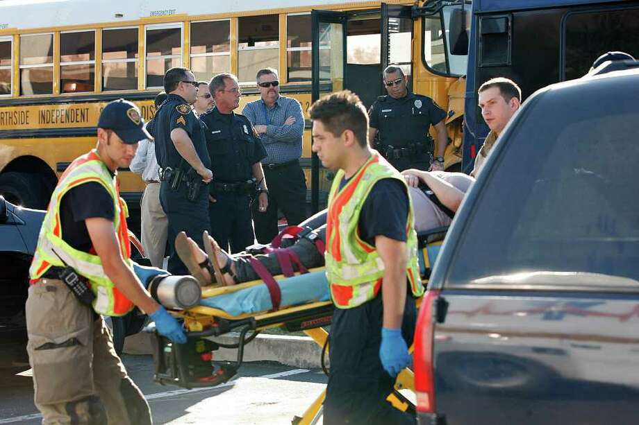 METRO -- Northside police officers look on as San Antonio emergency personnel transport victims of a two-bus accident along westbound access road of Northwest Loop 410 near Exchange Parkway, Tuesday, April 12, 2011. Nine people suffered injuries not thought to be life-threatening Tuesday morning, when an empty Northside Independent School District bus rear-ended a VIA Metropolitan Transit bus on the Northwest Side. The crash took place around 8 a.m.  JERRY LARA/glara@express-news.net Photo: JERRY LARA, SAN ANTONIO EXPRESS-NEWS / SAN ANTONIO EXPRESS-NEWS