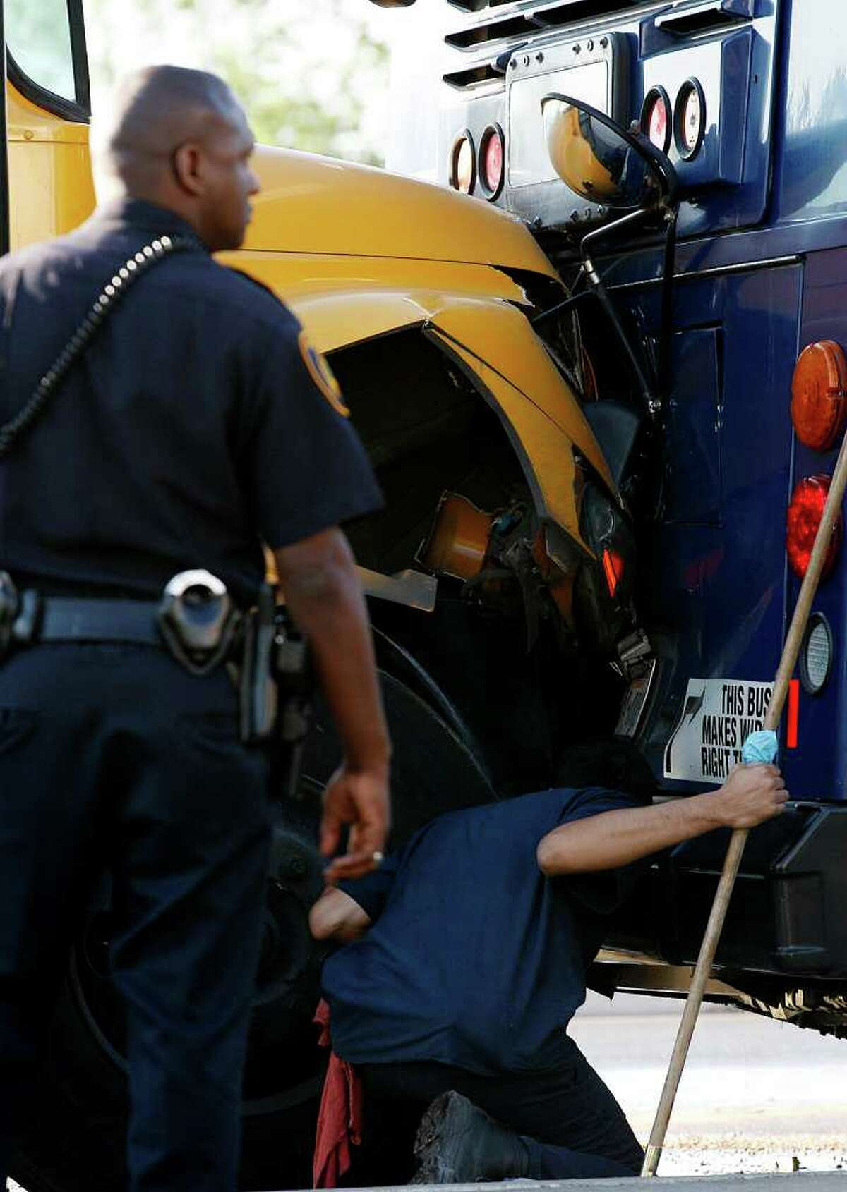 METRO -- A tow truck driver prepares to separate the vechicles at the scene of a two-bus accident along westbound access road of Northwest Loop 410 near Exchange Parkway, Tuesday, April 12, 2011. Nine people suffered injuries not thought to be life-threatening Tuesday morning, when an empty Northside Independent School District bus rear-ended a VIA Metropolitan Transit bus on the Northwest Side. The crash took place around 8 a.m. JERRY LARA/glara@express-news.net