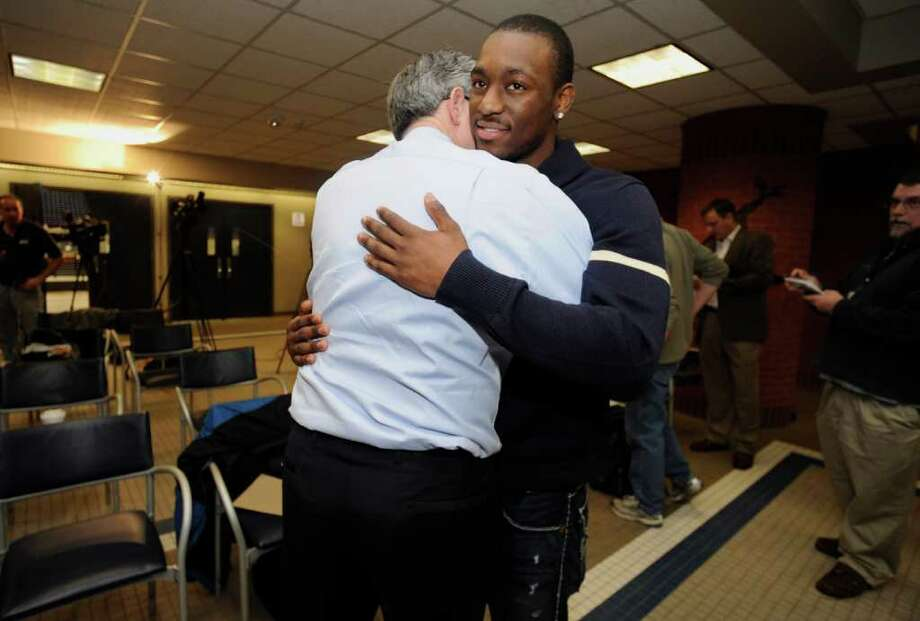 Connecticut's Kemba Walker, right, hugs athletic director Jeff Hathaway, left, after announcing his intention to enter the 2011 NBA draft during a news conference in Storrs, Conn., Tuesday, April 12, 2011. (AP Photo/Jessica Hill) Photo: AP
