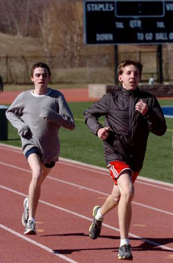 Staples senior captain Jack Roche, left, and junior Mik Kulis run during a preseason practice. The Wreckers won their first meet of the season last Thursday, 106-44 over Greenwich. Photo: Christian Abraham / Staff Photographer