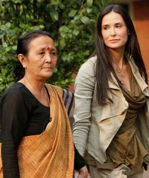 Hollywood actress Demi Moore (R) and Maiti Nepal Chairperson Anuradha Koirala (L) walk to a press conference at the end of her six days long visit at Maiti Nepal, a rehabilitation and orphanage home for HIV-affected children and women who are victims of trafficking in Kathmandu on April 7, 2011. The 48-year-old actress takes part in The CNN's Freedom Project, a worldwide network which works to eliminate trafficking and sex slavery. Moore worked with the biggest Nepalese anti-trafficking NGO whose founder Nuradha Koirala won an online poll to become The CNN's Hero Of The Year. AFP PHOTO/ Prakash MATHEMA Photo: AFP/Getty Images