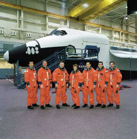 Posing in front of the full-fuselage traininer on Nov. 12, 2002 at Johnson Space Center, in Houston, are (from left) mission specialists Soichi Noguchi and Stephen Robinson, pilot James M. Kelly, mission Commander Eileen Collins and flight engineer Edward Lu, mission Commander Yuri Malenchenko and flight engineer Alexander Kaleri. Photo: NASA / False