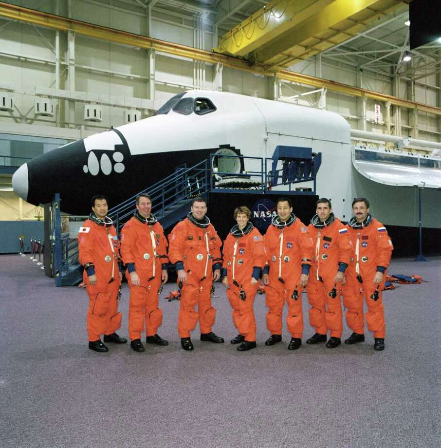 NASA's STS-114 and Expedition Seven crews, attired in training versions of the full-pressure launch and entry suit, pose for a group photo in front of the full-fuselage trainer prior to a training session on Nov. 12, 2002 in the Space Vehicle Mockup Facility at the Johnson Space Center, in Houston. From the left are astronauts Soichi Noguchi, Stephen K. Robinson, both STS-114 mission specialists; James M. Kelly, STS-114 pilot; Eileen M. Collins, STS-114 mission commander; Edward T. Lu, Expedition Seven flight engineer; cosmonauts Yuri I. Malenchenko, Expedition Seven mission commander; and Alexander Y. Kaleri, Expedition Seven flight engineer. Noguchi represents Japan's National Space Development Agency. Malenchenko and Kaleri represent Rosaviakosmos. Photo: NASA / False