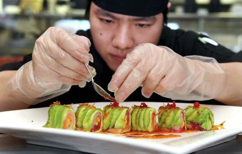 Jin Jiang, executive sushi chef at JKoo in Newtown, sprinkles red caviar on a Rainbow Avocado dish, an appetizer served at the restaurant. Photo taken Wednesday, April 6, 2011. Photo: Carol Kaliff / The News-Times