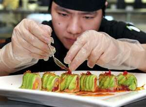 Jin Jiang, executive sushi chef at JKoo in Newtown, sprinkles red caviar on a Rainbow Avocado dish, an appetizer served at the restaurant. Photo taken Wednesday, April 6, 2011.