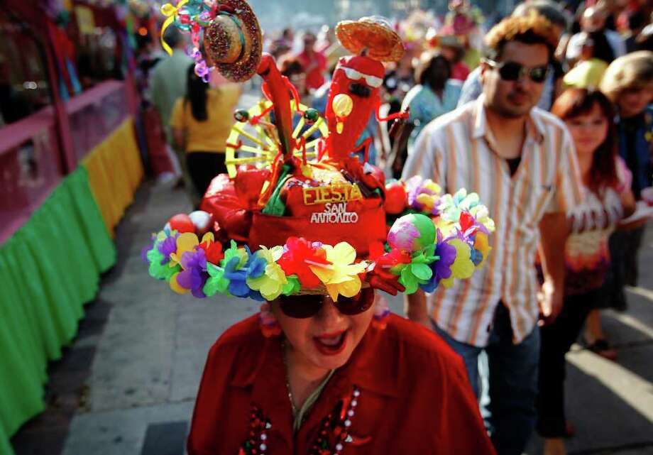 Lupe Medrano wears a hat she made with symbols of chiles and cascarones at the opening of A Night in Old San Antonio at La Villita on Tuesday. Medrano said she wanted to symbolize all the things she loves about Fiesta. Photo: Kin Man Hui/kmhui@express-news.net / San Antonio Express-News