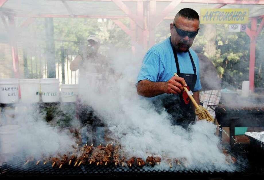 Gilbert Mancha gets enveloped in a cloud of smoke while basting a row of anticuchos, or cubes of skewered meat, at NIOSA. The item is one of the more popular treats at the event, he says. Photo: Kin Man Hui/kmhui@express-news.net / San Antonio Express-News