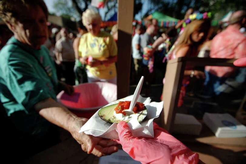 A guest is handed an aguacates - an avacado served with sour cream and salsa - at the opening of