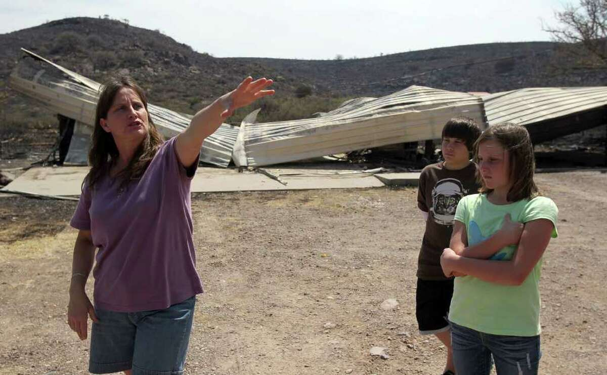 Tiffany Roman (left) of Fort Davis speaks Tuesday, April 12, 2011, about the wildfires that swept through the area destroying some her property (background). Roman said she was grateful that her home was intact, despite losing a garage and carport storage area. On the right are two of her children, Luke Roman, 12, and Katelynn Roman,11.