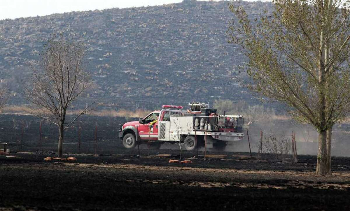 A brush truck checks for hot spots Tuesday April 12, 2011, near Fort Davis after wildfires swept through the area charring thousands of acres of land and destroying 25 structures in Fort Davis and two homes in Marfa.