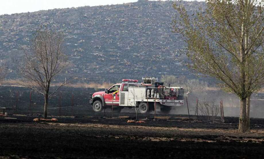 A brush truck checks for hot spots Tuesday April 12, 2011, near Fort Davis after wildfires swept through the area charring thousands of acres of land and destroying 25 structures in Fort Davis and two homes in Marfa. Photo: John Davenport/Express-News