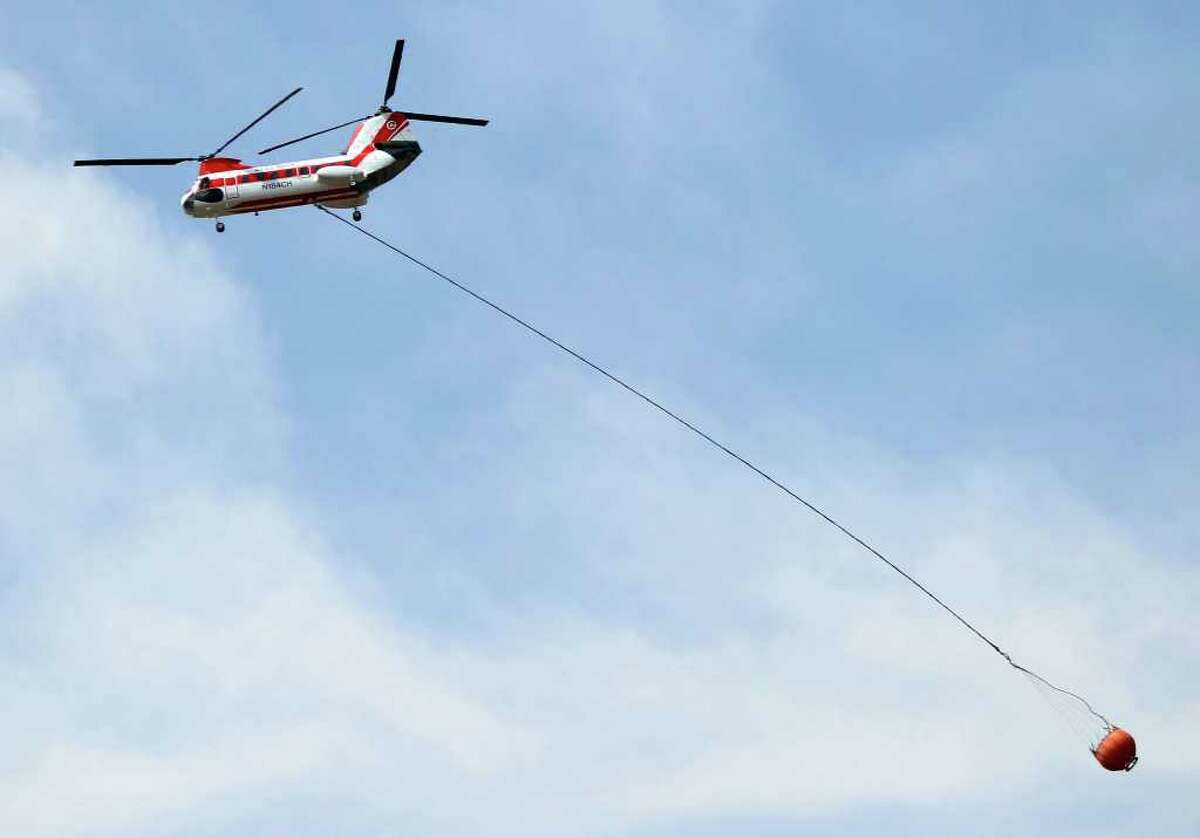 A helicopter leaves the scene of one of the fires still burning in West Texas near Fort Davis on Tuesday, April 12, 2011.