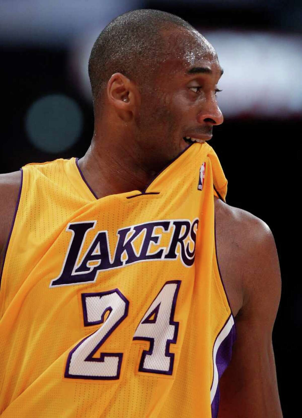 Los Angeles Lakers' Kobe Bryant bites his jersey during the first half of an NBA basketball game against the San Antonio Spurs in Los Angeles, Tuesday, April 12, 2011.