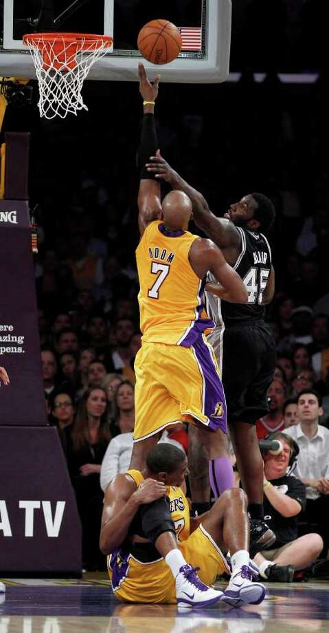 Los Angeles Lakers' Andrew Bynum holds his knee on the floor after being hurt as teammate Lamar Odom and San Antonio Spurs' DeJuan Blair reach for a rebound during the first half of a NBA basketball game in Los Angeles, Tuesday, April 12, 2011. Photo: AP
