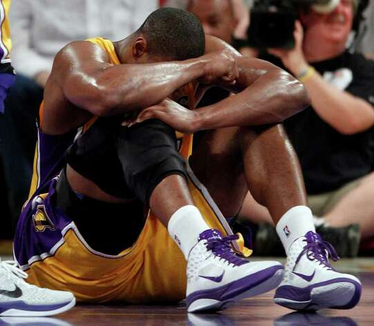 Los Angeles Lakers' Andrew Bynum holds his knee on the floor after being hurt during the first half of a NBA basketball game against the San Antonio Spurs in Los Angeles, Tuesday, April 12, 2011. Bynum hyperextended his right knee. Photo: AP