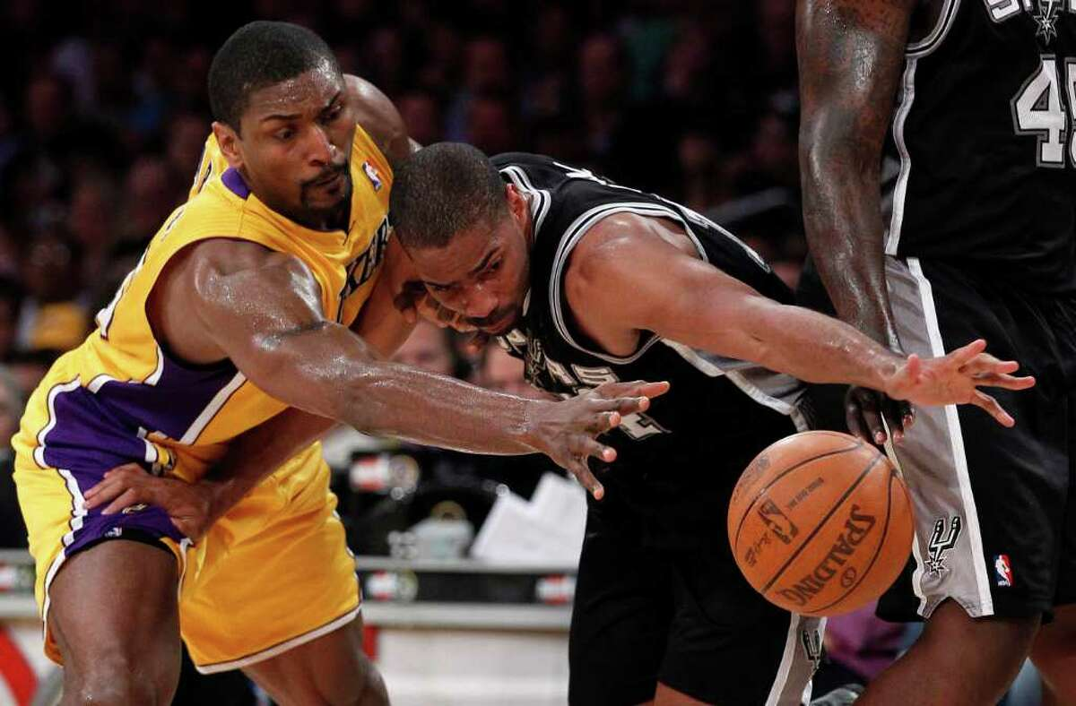 Los Angeles Lakers' Ron Artest, left, battles San Antonio Spurs' Gary Neal for a rebound during the second half of an NBA basketball game in Los Angeles, Tuesday, April 12, 2011.