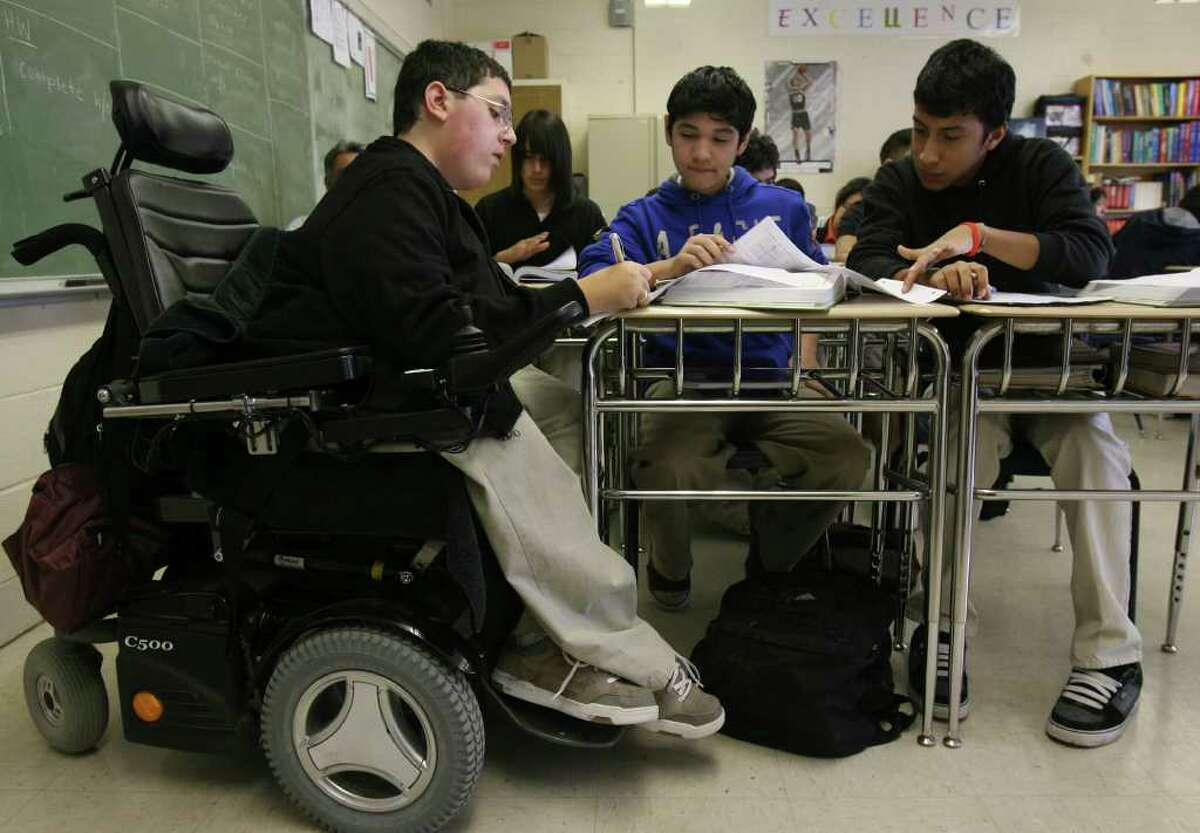Jonathon Stach,16, (left) reviews algebra with fellow students Christopher Aragon,15, and Guillermo Alvarado,16, (right) in class at Burbank High School. Stach has spinal muscular atrophy and is in Burbank's distinguished International Baccalaureate program and is getting credit in his P.E. class by being a scorekeeper for the school's freshman basketball team. JOHN DAVENPORT/jdavenport@express-news.net