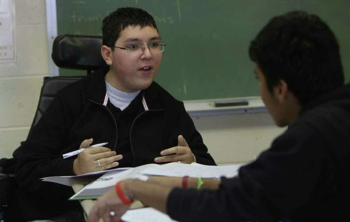 Jonathon Stach,16, (facing) reviews algebra with fellow student Guillermo Alvarado,16, in class at Burbank High School. Stach has spinal muscular atrophy and is in Burbank's distinguished International Baccalaureate program. JOHN DAVENPORT/jdavenport@express-news.net