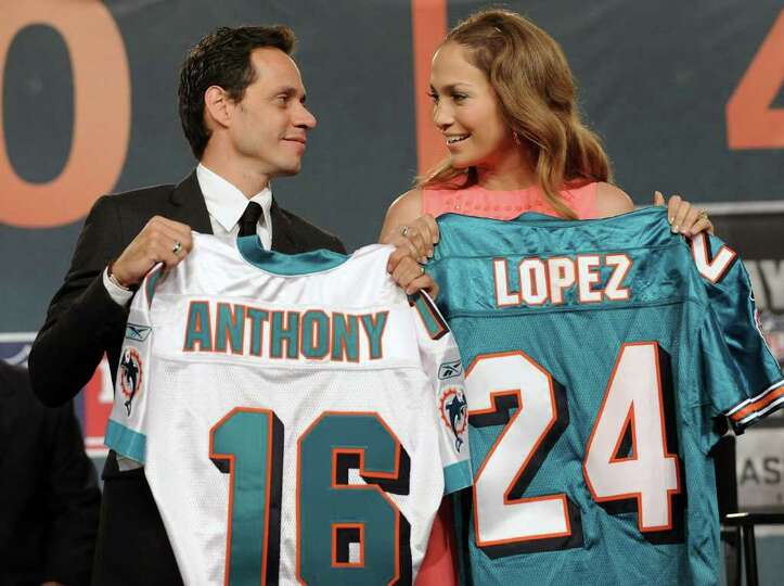 Singer Marc Anthony and his wife actress Jennifer Lopez hold up Miami Dolphins jerseys during a news