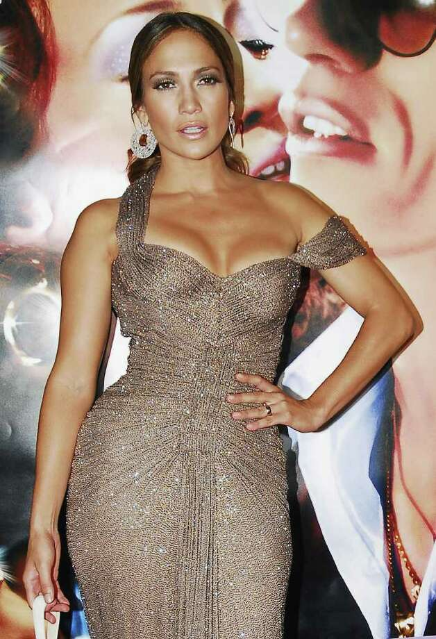 """Actress-singer Jennifer Lopez poses for photographers on the red carpet for the movie premiere of """"El Cantante,"""" or """"The Singer,"""" a film biography of salsa-music pioneer Hector Lavoe, in San Juan, Puerto Rico, Monday, July 23, 2007. Lopez's husband, Marc Anthony, starred as the famed but troubled Puerto Rican singer and Lopez played the singer's long-suffering wife, Puchi. Photo: Herminio Rodriguez, AP / AP"""