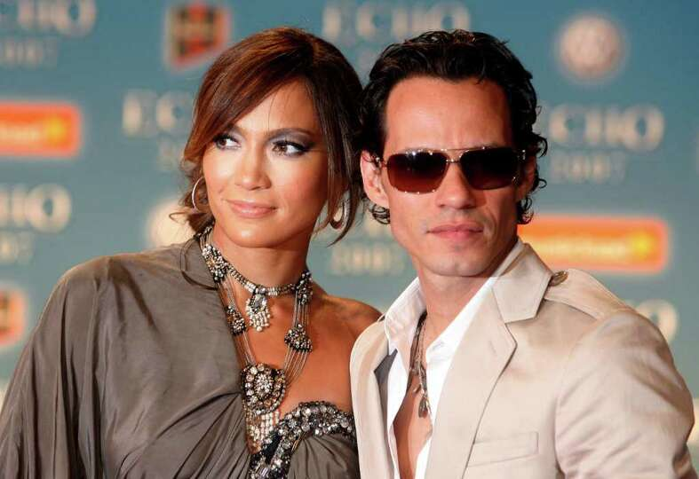 US Actress Jennifer Lopez, left, and her husband Marc Anthony, right, pose during their arrival for