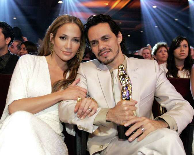 Singer Marc Anthony sits with his wife actress Jennifer Lopez after he received the Celia Cruz award