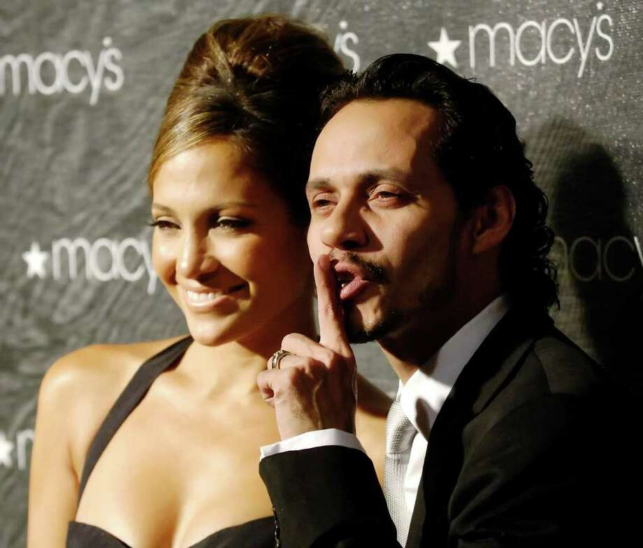 Singer Marc Anthony signals for photographers to quiet down as his wife, Jennifer Lopez, looks on at the Macy's Passport HIV/AIDS fundraiser and fashion show at Barker Hangar in Santa Monica, Calif., Thursday, Sept. 29, 2005. Lopez debuted the fall line of clothes from her JLO collection at the show. Photo: CHRIS PIZZELLO, AP / AP