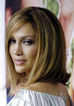 "** FILE ** Jennifer Lopez poses for photographers at the premiere of the film, ""Monster-in-Law"", in Los Angeles, in this April 29, 2005, file photo.  Lopez was in Puerto Rico this week to record a reggaeton song with rapper-producer Pharrell Williams.  The 37-year-old singer-actress arrived Tuesday, Aug. 30, 2005 to work on the track, which will be produced by top reggaeton duo LunyTunes, El Vocero and El Nuevo Dia newspapers reported. Photo: CHRIS PIZZELLO, AP / AP"