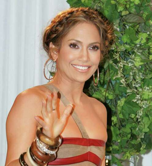 Jennifer Lopez waves at photographers as she arrives at a press conference promoting her new album