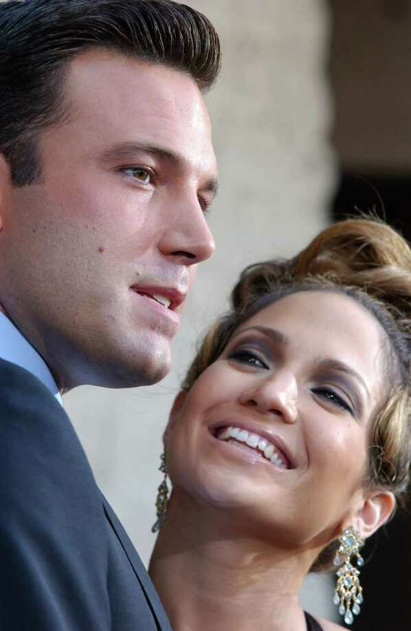 ** FILE ** Jennifer Lopez looks up at Ben Affleck as the two pose for photographers during their red carpet arrival at the premiere of their film Gigli, Sunday, July 27, 2003, in the Westwood section of Los Angeles. Accepting an award from the People for the American Way Foundation, a liberal foundation, Tuesday, Oct. 14, 2003, Affleck didnt use the f-word _ as in fiancee _ when referring Lopez. I only accept it in the hopes that the absurd amounts of publicity that I received lately, that as far as Ican tell is chiefly because I have a pretty girlfriend, thats what I did, I am a champion of the American way with a pretty girlfriend _ bring it on, paparazzi, news at 11 _ in the hopes that some of that publicity might be pointed at something more significant, something more positive, productive and meaningful, said Affleck, according to an Associated Press Television News tape. Affleck made the remarks while accepting a Spirit of Liberty Award Tuesday night in Los Angeles. Photo: RENE MACURA, AP / AP