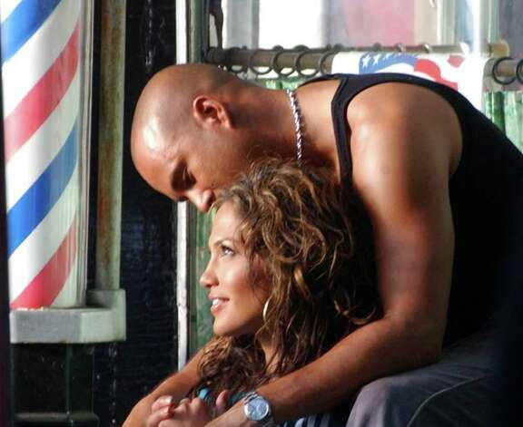 "Jennifer Lopez and husband Cris Judd sit with each other during filming of a scene together for her upcoming video, ""I'm Gonna Be Alright,""  after midnight in front of Claudia 's Barber Shop on East 117th Street in New York, Thursday April 18, 2002. (Photo/Amarjit Sidhu) Photo: AMARJIT SIDHU, AP / AP"