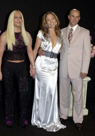 Italian fashion designer Donatella Versace, left, with actress and singer Jennifer Lopez and her husband, choreographer Cris Judd, smile prior to the start of the Versace Spring-Summer 2002 fashions in Milan, Italy,  Tuesday, Oct. 2 , 2001.  Lopez, who married in California last Saturday, Sept. 29, and her husband are honeymooning in Italy. Photo: LUCA BRUNO, AP / AP