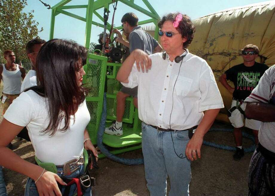 FOR LIFESTYLE ADVANCE--Writer/director Gregory Nava (left) talks with Jennifer Lopez about a shot being filmed at Splashtown in San Antonio with a bungee jump (bungee cage in background).  Lopez will play the Tejano superstar Slena in the upcoming movie.  Rick Hunter/Staff Photo: RICK HUNTER, File 96-