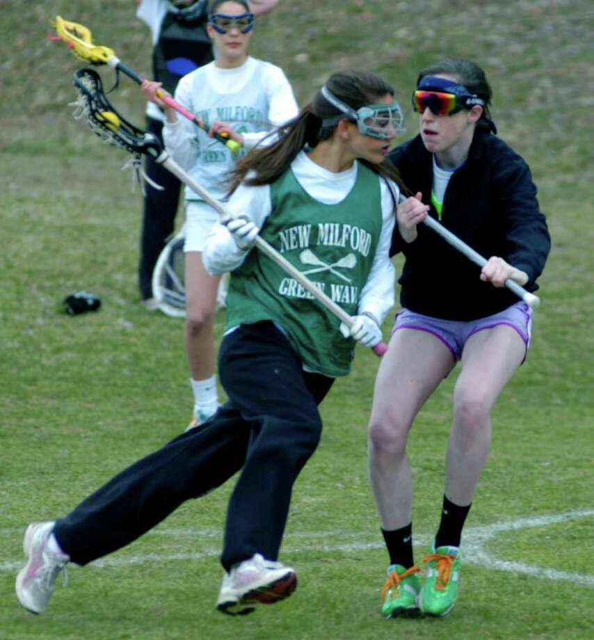 SPECTRUM/Cristina Munoz of New Milford High School girls' lacrosse has teammate Olivia Monteiro on her toes during a pre-season drill as Destinee Carey checks out their technique. April 2011 Photo: Norm Cummings / The News-Times