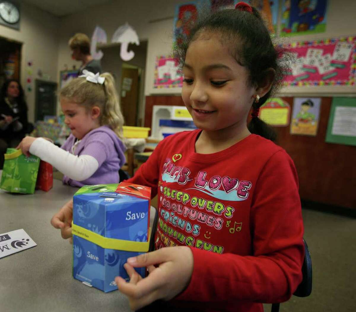 Kindergartener Karina Delgado assembles a moon jar, a three compartment savings bank, during Financial Literacy Day at Lordship School in Stratford on Wednesday, April 13, 2011.