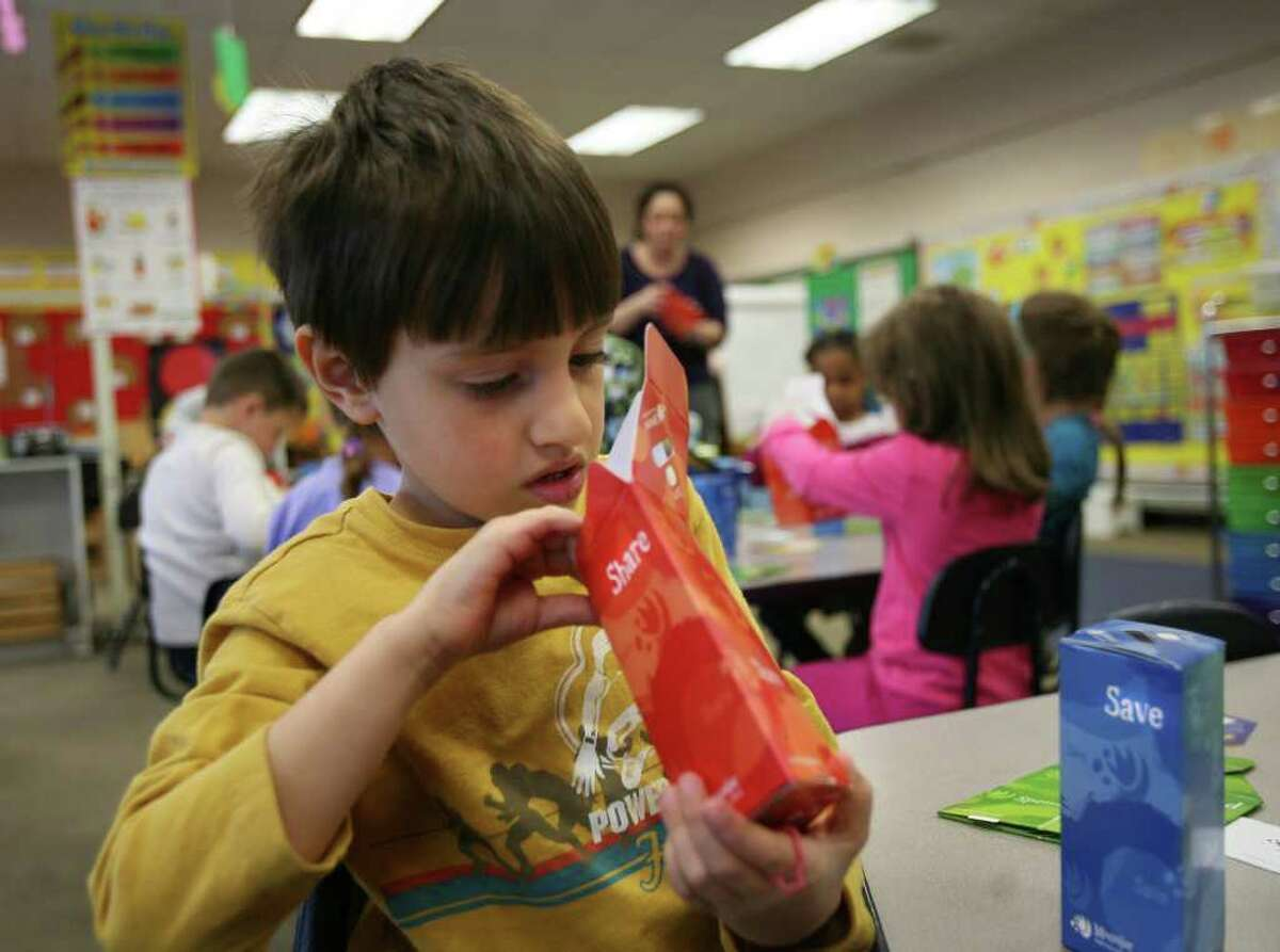Kindergartener Simon Fernandes assembles a moon jar, a three compartment savings bank, during Financial Literacy Day at Lordship School in Stratford on Wednesday, April 13, 2011.