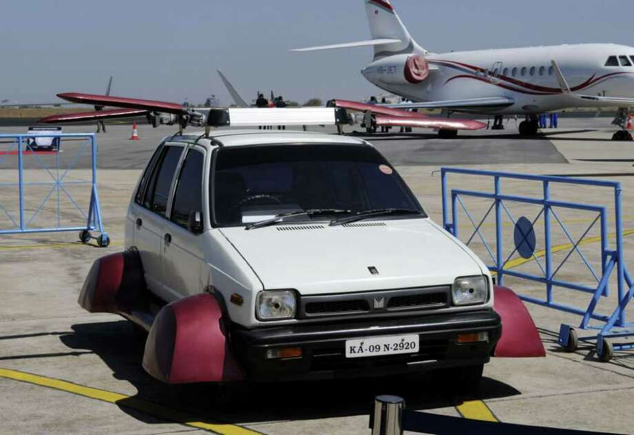 "A prototype of a flying car, called the ""Flying Maruti"" and developed by Indian innovator A. K. Vishwanath, sits on the tarmac at the Aero India 2011 air show in Bangalore on Feb. 11, 2011.  Unassumingly parked next to some of the world's most lethal warplanes, the squat, converted, 800cc Maruti hatchback stole some of the thunder from the supersonic exhibits. But it's a far cry from the flying vehicles in ""The Jetsons."" Photo: STR, STR/AFP/Getty Images / 2011 AFP"