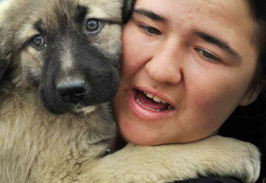A Romanian woman holds a puppy during a protest for animal rights in front of the Romanian parliamen