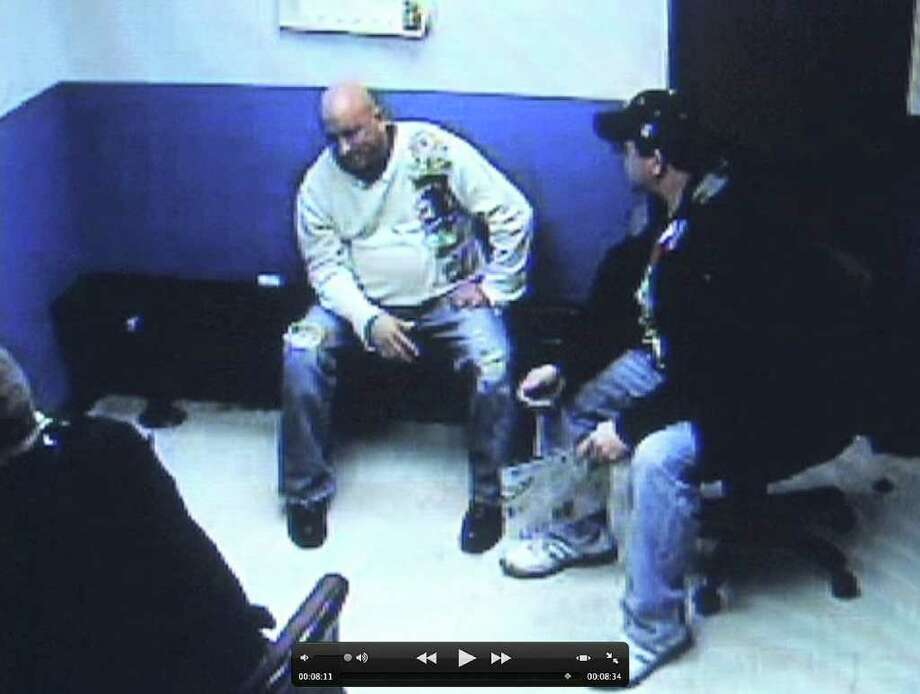 Frame grab from stationhouse video footage of the arrest of Albany police officer Brian Lutz, left, in Menands. Christian Mesley, the former Albany police union president, is at right.