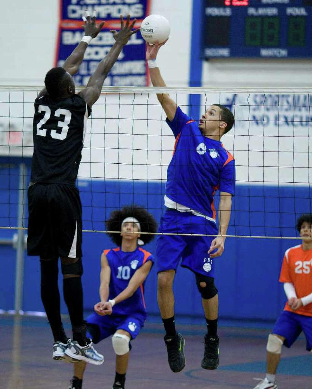Danbury's Denzel Wilkins returns a shot over Bridgeport Central's Abdoulie Williams Wednesday at Danbury High School.