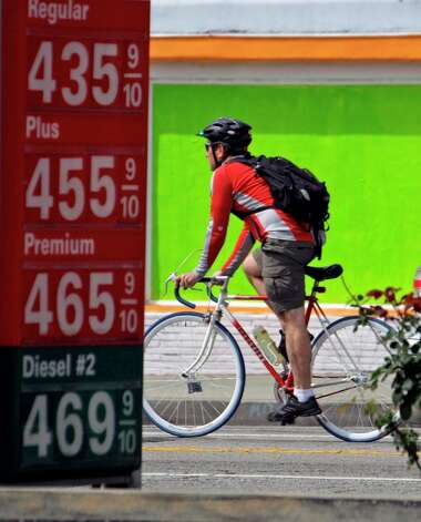 A bicyclist passes a 76 station with fuel prices in the $4 range in Los Angeles on April 11, 2011. On April 13, the average cost of a gallon of regular unleaded gasoline for the U.S. was $3.80. Locally the cost was $3.66. Photo: AP Photo/Reed Saxon